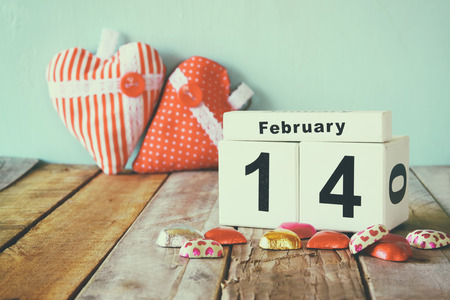 14th: February 14th wooden vintage calendar with colorful heart shape chocolates on wooden table. selective focus. vintage filtered