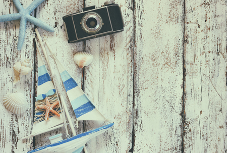 view on sea: top view image of photo camera, wood boat, sea shells and star fish over wooden table