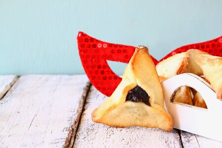 hamantasch: Hamantaschen cookies or hamans ears and red mask Purim celebration jewish carnival holiday. selective focus Stock Photo