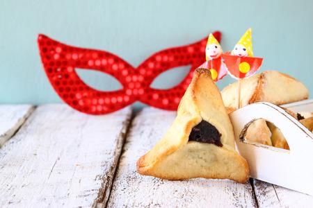 hamantashen: Hamantaschen cookies or hamans ears and red mask Purim celebration jewish carnival holiday. selective focus Stock Photo