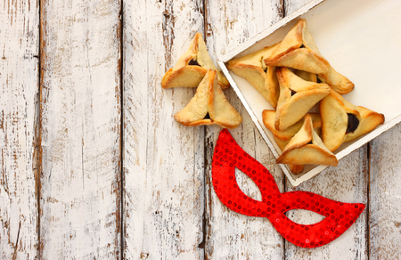 jewish: Hamantaschen cookies or hamans ears next to red mask Purim celebration jewish carnival holiday. selective focus Stock Photo