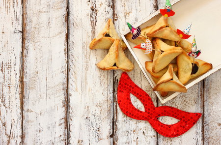 purim mask: Hamantaschen cookies or hamans ears next to red mask Purim celebration jewish carnival holiday. selective focus Stock Photo