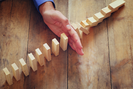 concetto: una mano maschile stoping l'effetto domino. immagine retrò stile esecutivo e il concetto di controllo del rischio