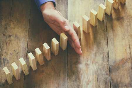 domino effect: a male hand stoping the domino effect. retro style image executive and risk control concept Stock Photo