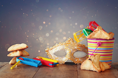 jewish: Hamantaschen cookies or hamans ears,noisemaker and mask for Purim celebration jewish carnival holiday and glitter background. selective focus Stock Photo