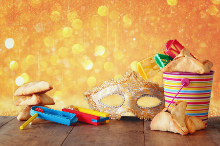 jewish background: Hamantaschen cookies or hamans ears,noisemaker and mask for Purim celebration jewish carnival holiday and glitter background. selective focus Stock Photo