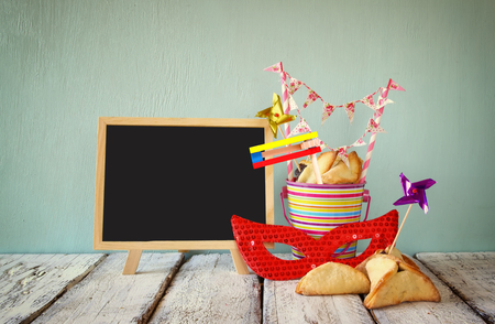 hamantaschen: Hamantaschen cookies or hamans ears,noisemaker and mask next to blackboard for Purim celebration jewish carnival holiday. selective focus