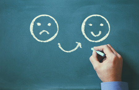 sad smiley: male hand drawing unhappy and happy smileys faces on chalkboard