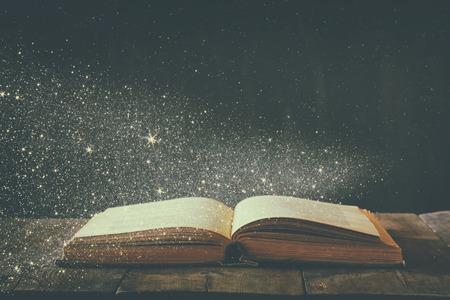 나무 테이블에 오픈 골동품 책의 추상적 인 이미지. 선택적 포커스. 복고풍 여과하고 반짝이 오버레이 톤