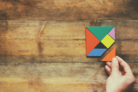 solve problems: mans hand holding a missing piece in a square tangram puzzle, over wooden table.