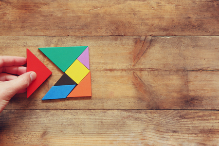 man's hand holding a missing piece in a square tangram puzzle, over wooden table. Imagens - 50654467