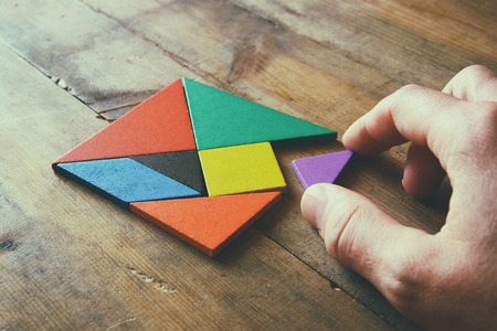 business asia: mans hand holding a missing piece in a square tangram puzzle, over wooden table.