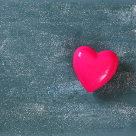 plastic heart: top view image of pink plastic heart on blackboard background. valentines day celebration concept