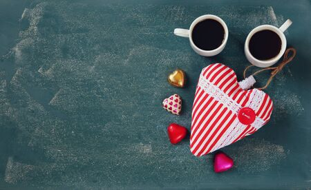 cafe bombon: top view image of colorful heart shape chocolates, fabric heart and couple mugs of coffee on blackboard background. valentines day celebration concept
