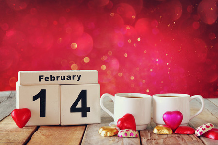 14th: February 14th wooden vintage calendar with colorful heart shape chocolates next to couple cups on wooden table. selective focus. vintage filtered