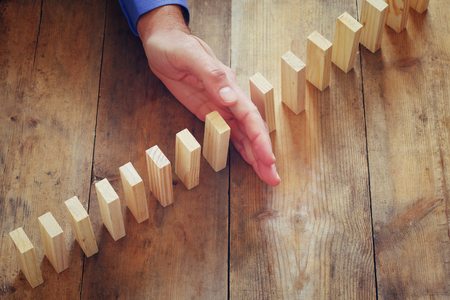 fragile economy: a male hand stoping the domino effect. retro style image executive and risk control concept Stock Photo