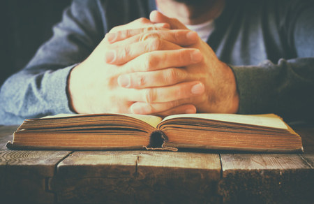 hand hold: low key image of person sitting next to prayer book