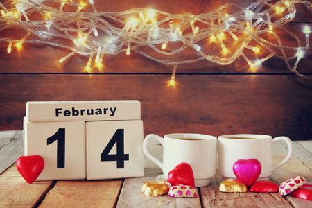 february 14th: February 14th wooden vintage calendar with colorful heart shape chocolates next to couple cups on wooden table. selective focus. vintage filtered