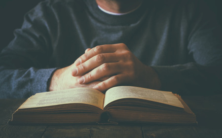 meditation help: low key image of person sitting next to prayer book