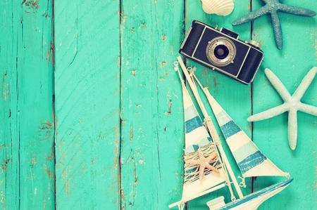 Imagen de la visión superior de la cámara de fotos, barco de madera, conchas de mar y estrellas de mar sobre la mesa de madera Foto de archivo