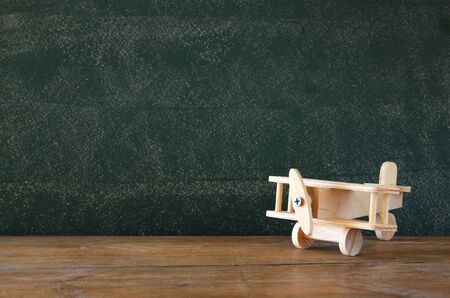 wooden toy: close up photo of wooden toy airplane against chalkboard Stock Photo