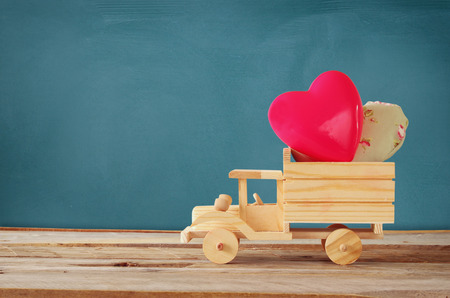 Photo Of Wooden Toy Truck With Hearts In Front Of Chalkboard. Valentines  Day Celebration Concept