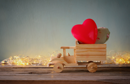 wooden toy: photo of wooden toy truck with hearts in front of chalkboard. valentines day celebration concept. vintage filtered Stock Photo