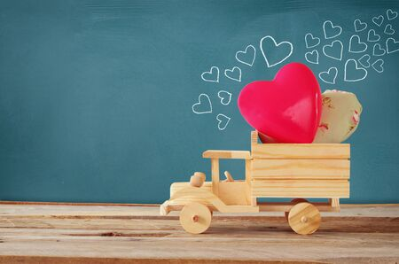 toy truck: photo of wooden toy truck with hearts in front of chalkboard. valentines day celebration concept. vintage filtered Stock Photo