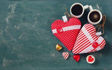cafe bombon: Imagen de la visión superior de chocolates en forma de corazón de colores y par de tazas de café en el fondo de la pizarra. celebración concepto día de San Valentín