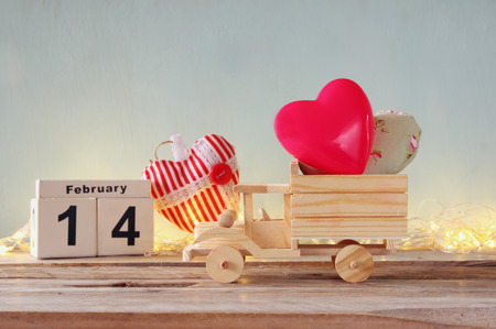 february 14th: February 14th wooden vintage calendar with wooden toy truck with hearts in front of chalkboard. valentines day celebration concept. vintage filtered