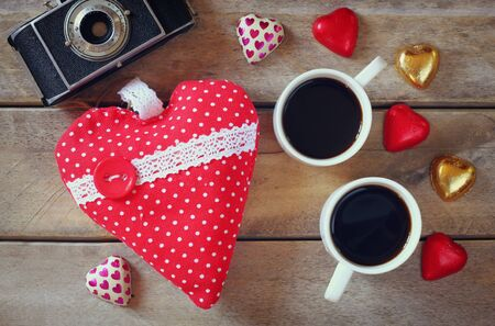 cafe bombon: top view image of colorful heart shape chocolates, fabric heart, vintage photo camera and cup of coffee on wooden table. valentines day celebration concept