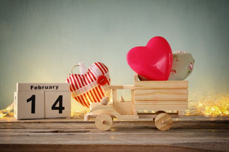 february 14th: low key e photo of February 14th wooden vintage calendar with wooden toy truck with hearts in front of chalkboard. valentines day celebration concept. vintage filtered