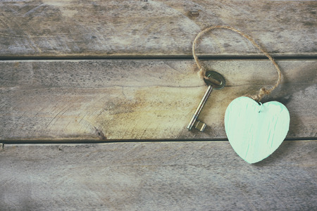 door lock love: top view of old vintage key with a wooden heart on wooden background