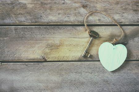 vista dall'alto della vecchia chiave vintage con un cuore di legno su sfondo di legno