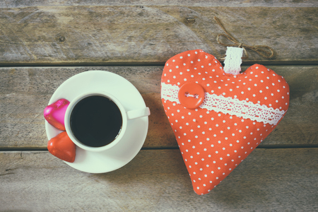 valentine          s day candy: top view image of colorful heart shape chocolates, fabric heart and cup of coffee on wooden table. valentines day celebration concept