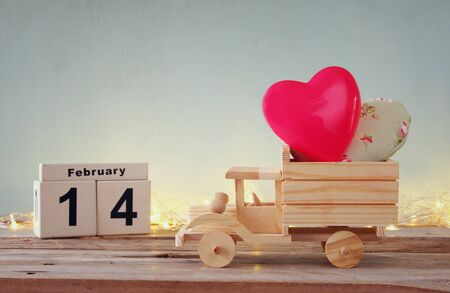 february 14th: low key photo of February 14th wooden vintage calendar with wooden toy truck with hearts in front of chalkboard. valentines day celebration concept.