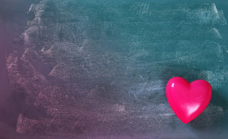 photo background: top view image of pink plastic heart on blackboard background. valentines day celebration concept. filtered and toned photo Stock Photo