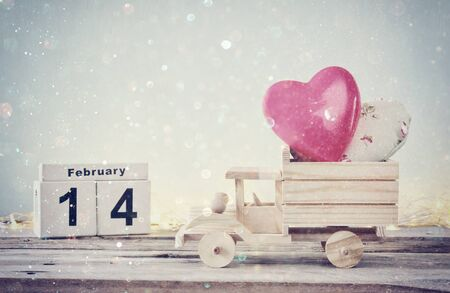 february 14th: low key photo of February 14th wooden vintage calendar with wooden toy truck with hearts in front of chalkboard. valentines day celebration concept. vintage filtered with glitter overlay Stock Photo