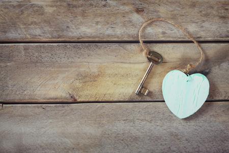 bovenaanzicht van oude vintage sleutel met een houten hart op houten achtergrond. retro gefilterd en afgezwakt