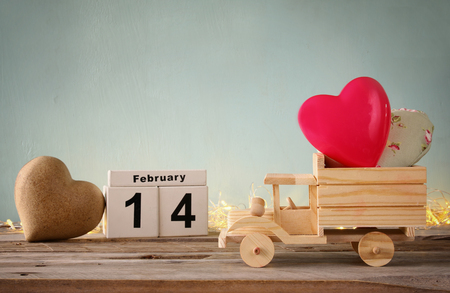 concept car: photo of wooden toy truck with hearts. valentines day celebration concept. vintage filtered Stock Photo