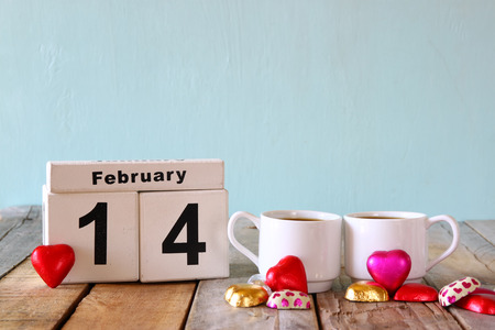 14 february: February 14th wooden vintage calendar with colorful heart shape chocolates next to couple cups on wooden table. selective focus. vintage filtered