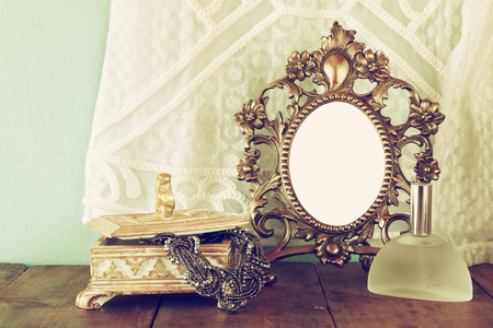 neckless: Antique blank victorian style frame, perfume bottle and neckless on wooden table. retro filtered image. template, ready to put photography