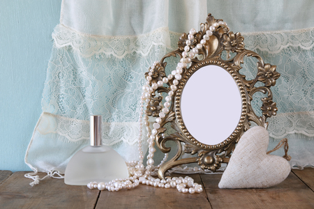 antique jewelry: Antique blank victorian style frame, perfume bottle and white pearls on wooden table. template, ready to put photography