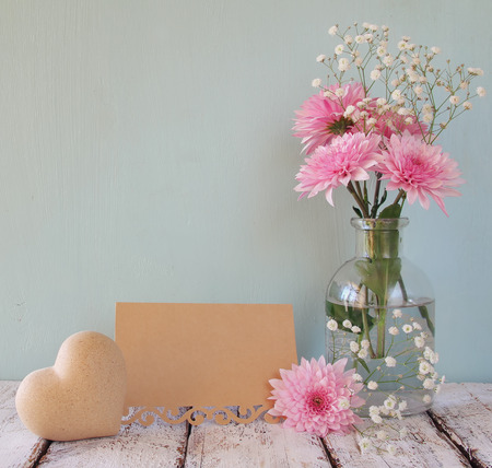 mothers day: fresh white and pink flowers, heart next to vintage empty card over wooden table Stock Photo