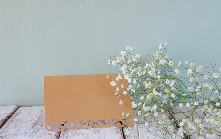 feminine: fresh white flowers next to vintage empty card over wooden table. vintage filtered and toned image