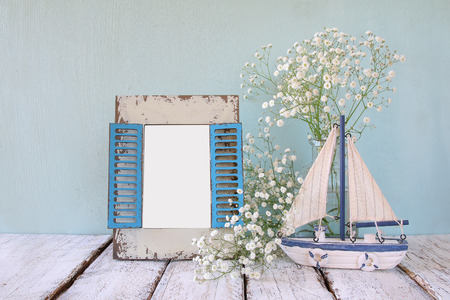 album: old vintage wooden frame, white flowers and sailing boat on wooden table. vintage filtered image. nautical lifestyle concept. template, ready to put photography