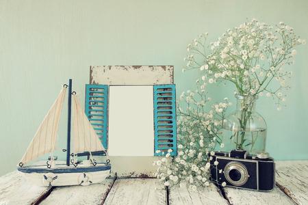 стиль жизни: старый старинный деревянный каркас, белые цветы, фото камеры и парусные лодки на деревянный стол. марочные отфильтрованного изображения. мореходное концепция образа жизни. шаблон, готовый поставить фотографию Фото со стока
