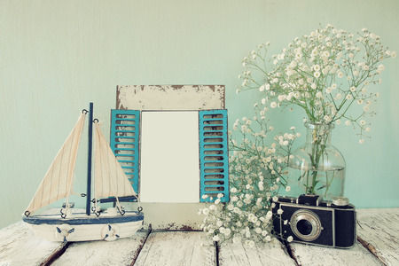 life style: old vintage wooden frame, white flowers, photo camera and sailing boat on wooden table. vintage filtered image. nautical lifestyle concept. template, ready to put photography