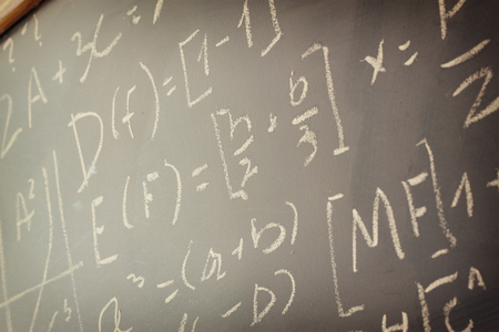 mathematical proof: side view of math formulas and calculation written over chalkboard. selective focus.