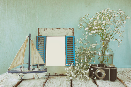decorative objects: old vintage wooden frame, white flowers, photo camera and sailing boat on wooden table. vintage filtered image. nautical lifestyle concept. template, ready to put photography